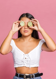 キウイで彼女の目を覆っている女性のミディアムショット