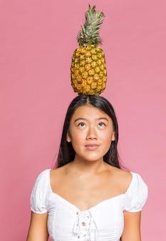 女性の頭の上にパイナップル