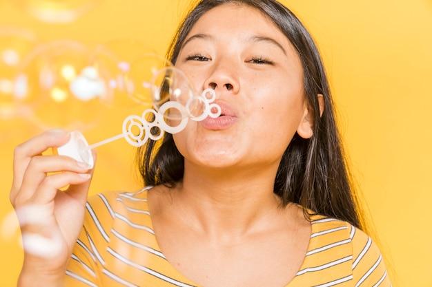 Женщина улыбается и делает пузыри