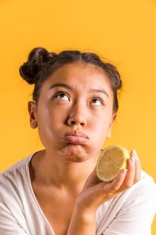 Женщина держит лимон и смотрит в сторону