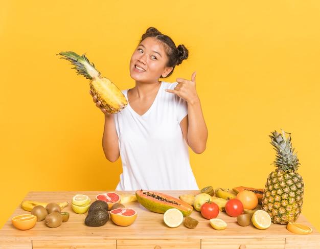 Женщина держит ананас и смотрит в сторону