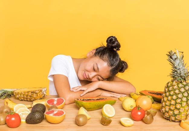 Женщина мечтательна в окружении фруктов