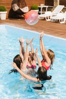 ビーチボールとスイミングプールで遊んでいる子供たち