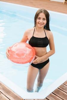 ビーチボールを保持している女性の子供の高いビュー