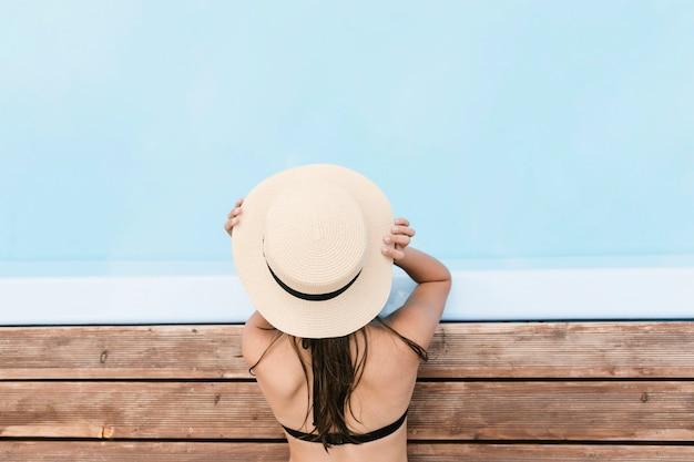 Девушка держит шляпу возле бассейна