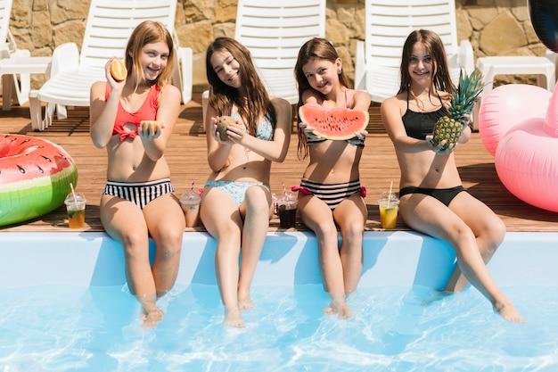 Счастливые девушки, показывающие разнообразие фруктов