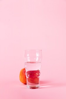 Стакан воды и нектарина на розовом фоне