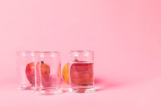 水で満たされたグラスの後ろにザクロ