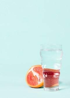 水のガラスとグレープフルーツの半分