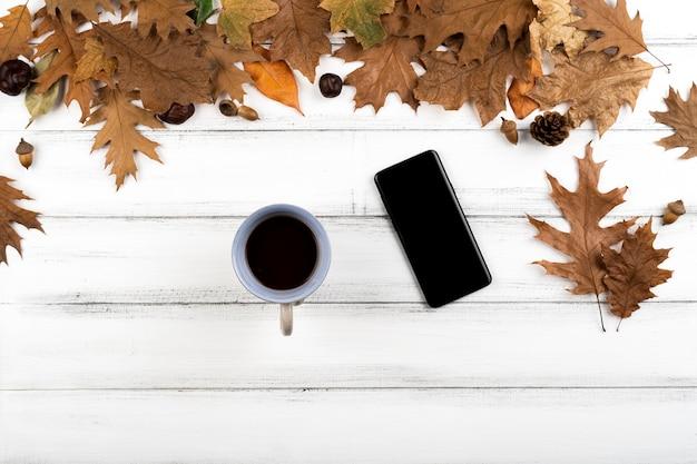 木製の葉の背景にスマートフォンとコーヒーカップ