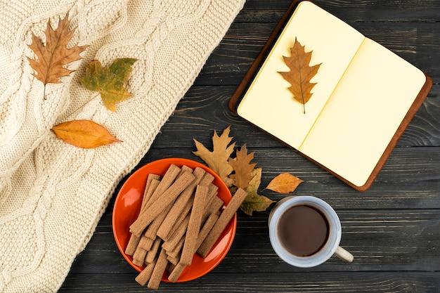 コーヒーと木製の背景上のノートブック