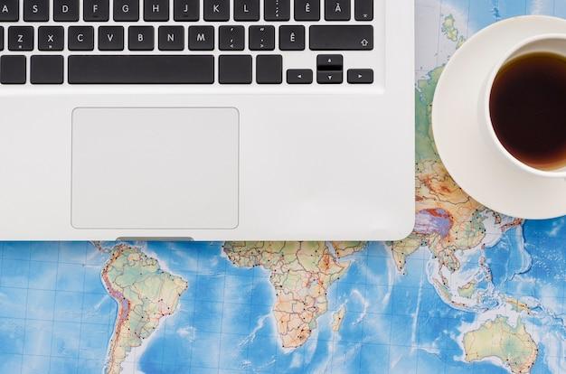 世界地図上のラップトップのフラットレイアウト