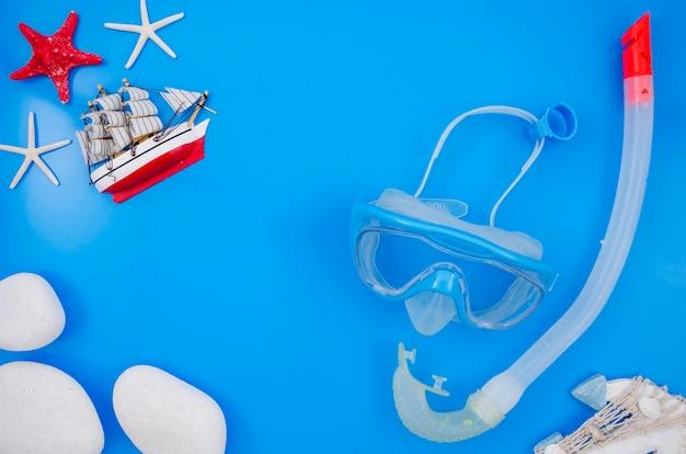 ダイビング用品と青色の背景のフラットレイアウト