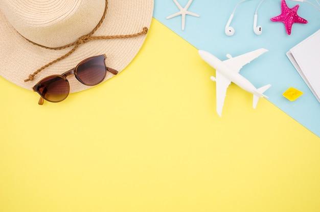 帽子とおもちゃの飛行機と黄色の背景のフラットレイアウト