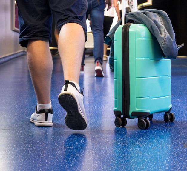 スーツケースを持つ男の背面図