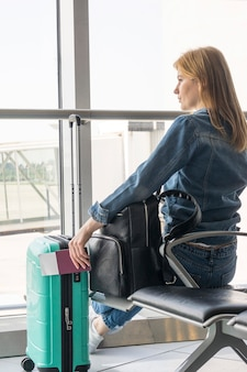 Вид сзади женщина ждет в аэропорту
