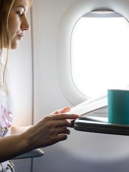 飛行機のメニューを探している女性