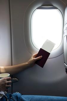 飛行機の窓の横にあるパスポートとチケット