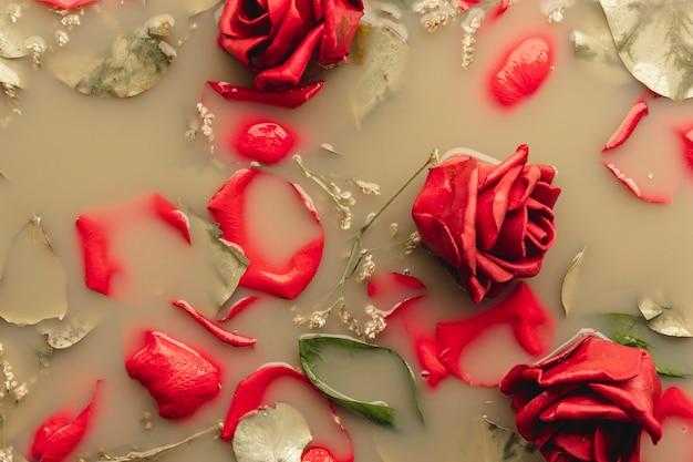 茶色の水に平干しの赤いバラと花びら