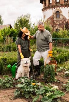 Пожилая пара в саду с собакой