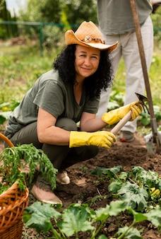 Старшая женщина заботится о посевах
