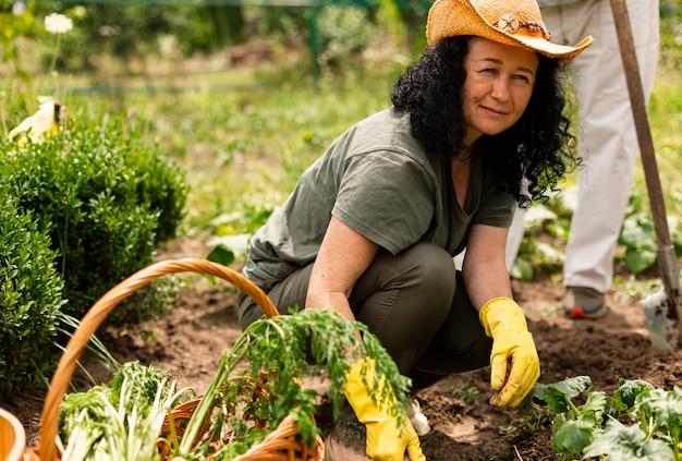作物を気遣う年配の女性