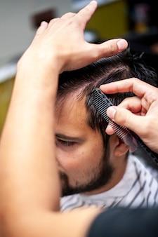 Парикмахер расчесывает волосы клиента высокий взгляд