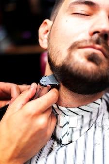 彼のひげを整える男