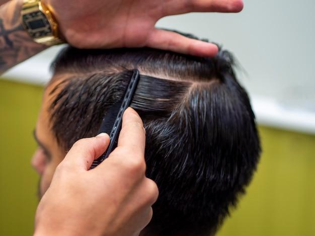 Парикмахер делает укладку волос на волосы своего клиента