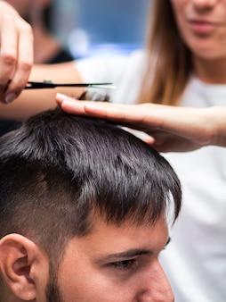 Женщина подстригает волосы клиента