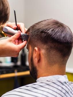 Мужчина подстригает волосы сзади