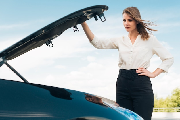 車のボンネットを開く女性のミディアムショット