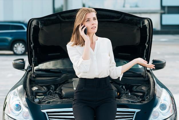 車と電話で話している女性