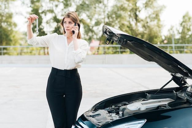 Женщина разговаривает по телефону и черный автомобиль