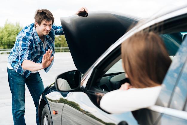 エンジンと車に座っている女性をチェックする男