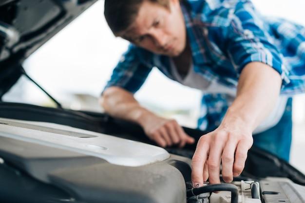 エンジンを修理する男のクローズアップ