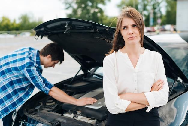 車のエンジンで作業する人