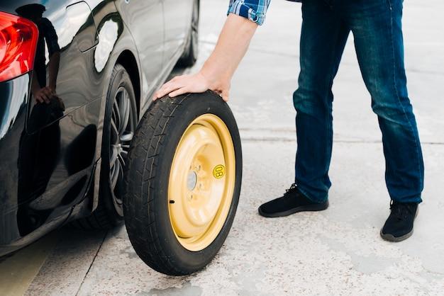 スペアタイヤと車のタイヤを変更する男