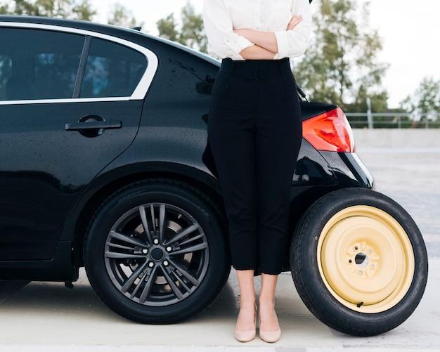 スペアタイヤを持つ女性の正面図
