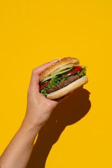 黄色の背景の前で食欲をそそるハンバーガー