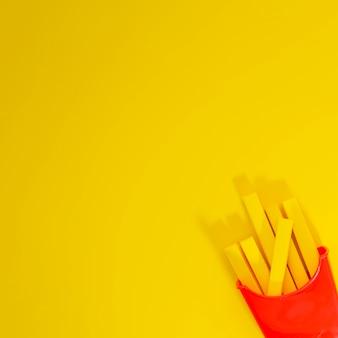 黄色の背景にフライドポテトのレプリカ