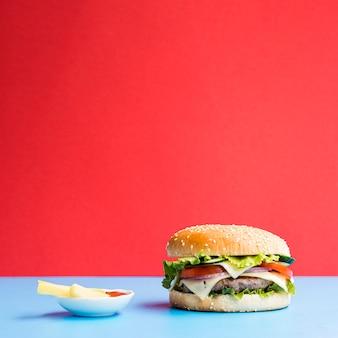 背景が赤の青いテーブルのハンバーガー