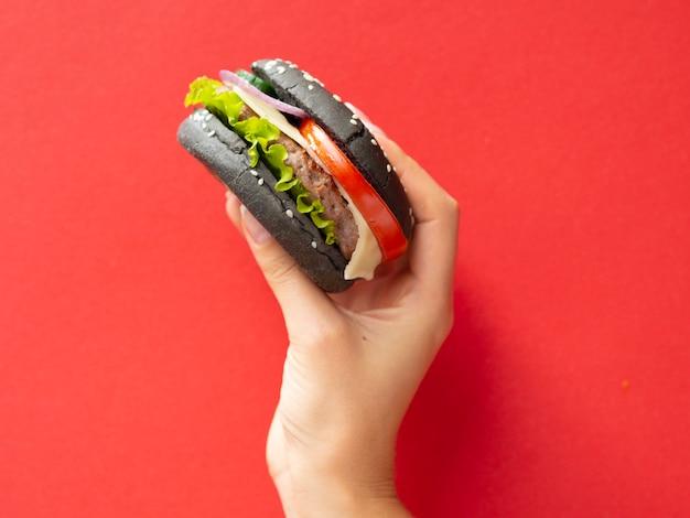 赤い背景のおいしいハンバーガーを上げる手