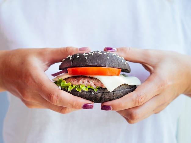 おいしいハンバーガーを示すクローズアップ手