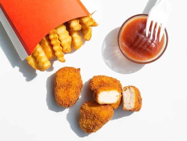 Вид сверху картофель фри с кетчупом и наггетсами