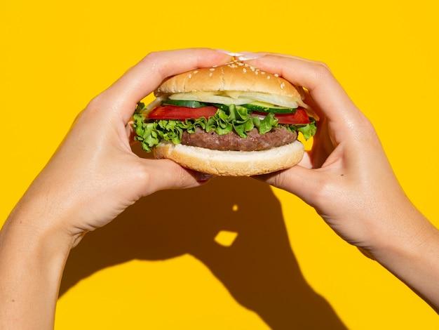 黄色の背景に完璧なハンバーガーを保持手