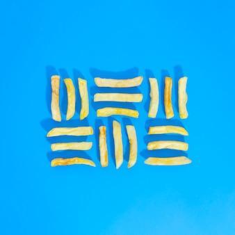 青の背景に並んでフライドポテトのフラットレイアウト