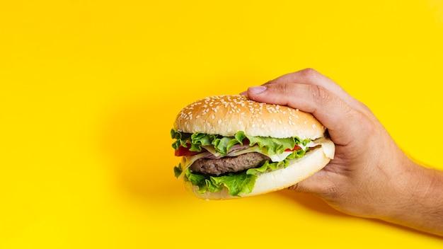 黄色の背景の前にハンバーガーを持って男