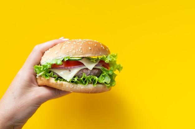 黄色の背景の前にハンバーガー