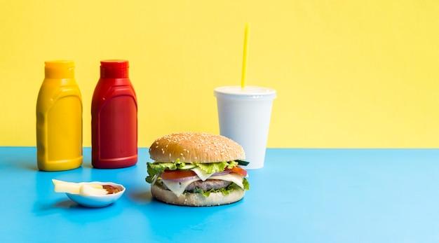 青いテーブルの上のソーダとハンバーガー